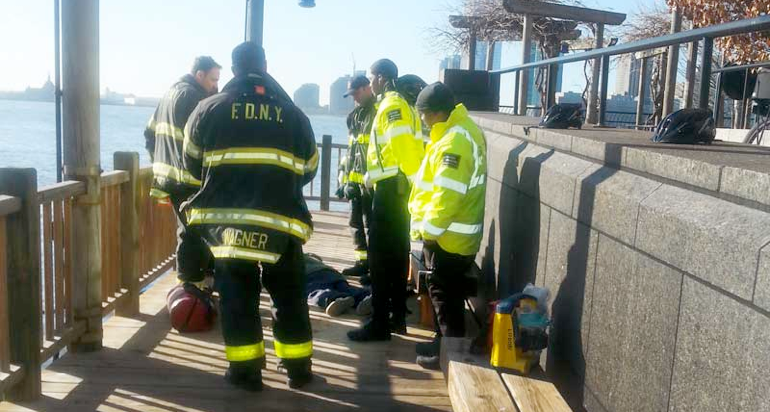 Fire fighters, emergency medical technicians, and AlliedBarton 'Ambassadors' surround an emotionally disturbed homeless man, who collapsed on the deck beside South Cove, after menacing several residents on Monday.