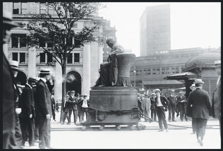 On June 19, 1916, Horace Greeley finally heeded his own advice and went west. Ousted from his niche in the Tribune Building by a city ordinance, public outcry kept the Tribune's founder from moving to Central Park and appropriately kept him in sight of Printing House Square. In this photo, Greeley appears to be supervising his own move to City Hall Park.