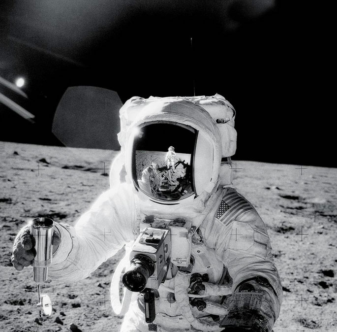 Apollo 12 astronaut Alan Bean holds a environmental sample container filled with lunar soil collected during his sojourn on the lunar surface. A Hasselblad camera is mounted on the chest of his spacesuit. Pete Conrad, who took this image, is reflected in Bean's helmet visor, Nov. 20, 1969