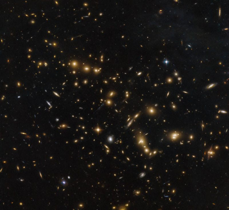 Galaxies look like fireflies, from EarthSky.org This image,  captured by the NASA/ESA Hubble Space Telescope, shows a massive group of galaxies bound together by gravity: a cluster named RXC J0032.1+1808. Image via ESA/Hubble & NASA, RELICS.