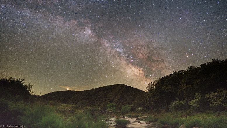 Mars shines brightly now in planet Earth's sky.  Seen with a yellowish hue it rises over the hills and far away in this serene night skyscape, a countryside panorama recorded last month from Parque Nacional de Cabaneros in Spain. The Milky Way too extends above the distant hills into a starry sky. Its faint pinkish nebulae, cosmic rifts and rivers of dust are mingled with the pale, diffuse glow of starlight. Mimicking Mars' yellow tint, bright star Antares shines to the right of the central Milky Way starclouds. photo: Jose Luis Hernandez Verdejo