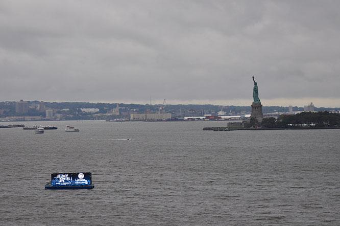 Ballyhoo Media's digital advertising catamaran in front of  the Statue of Liberty