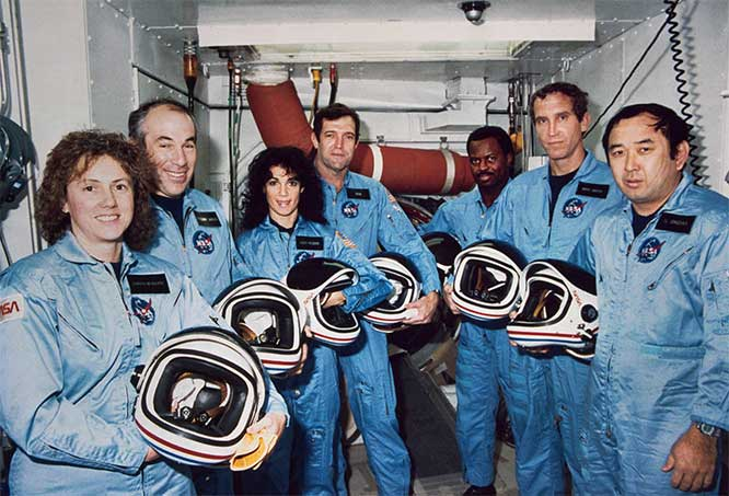 In this photo from Jan. 9, 1986 the Challenger crew takes a break during countdown training at NASA's Kennedy Space Center. Left to right are Teacher-in-Space payload specialist Sharon Christa McAuliffe; payload specialist Gregory Jarvis; and astronauts Judith A. Resnik, mission specialist;  Francis R. Scobee, mission commander; Ronald E. McNair and Ellison Onizuka engineer and astronaut. Image: NASA